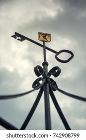 Forged cast iron key on a metal bow with a golden label with a dark sky in the background.
