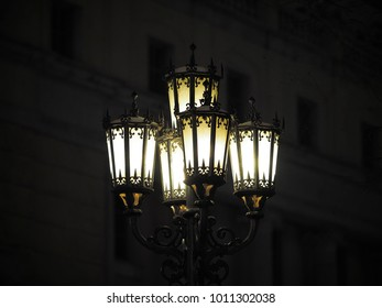 Forged five-domed wrought-iron street lamp in the evening city street; low key