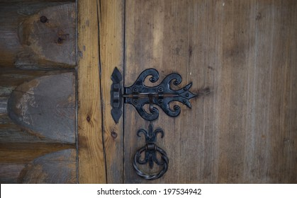 the forged handle and the lock on an old wooden door