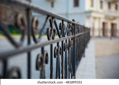 Forged metal fence on a city street. Soft selective focus. Blurred foreground and background.