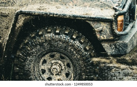 Forget about driving on smooth tarmac. Car racing offroad. Offroad car in action. Dirty car drive on high speed. SUV or offroader on mud road. Car wheels on steppe terrain splashing with dirt.