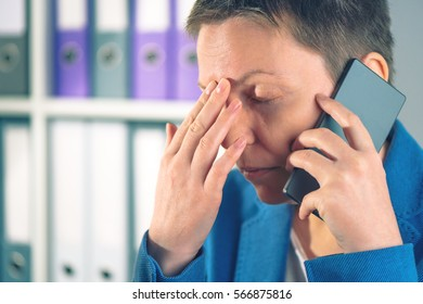 Forgetful businesswoman during mobile phone conversation, caucasian business female just realized that she forgot something