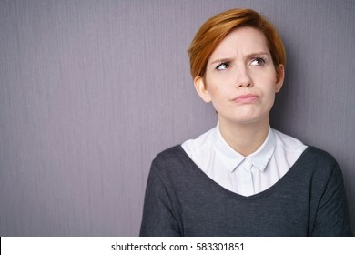 Forgetful young woman trying to remember something looking up into the air with a frown and grimace, over grey with copy space