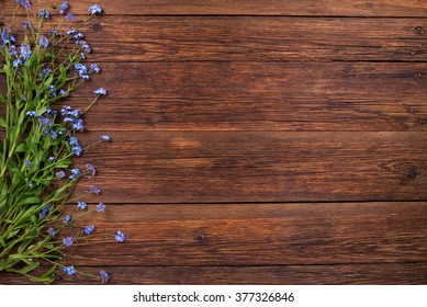 Forget-me-not blue flowers on wooden background, copy space