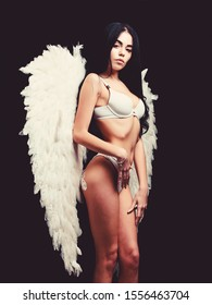 Forgive all sins. Attractive sensual woman angel wings. Erotic show. Femininity and sensuality. Angel feather wings accessory. Provoke sexual desire. Impeccable body. Fallen angel. Innocent pure girl.