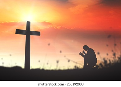Forgive and amazing grace concept: Silhouette christian kneeling and worship on cross sunset background