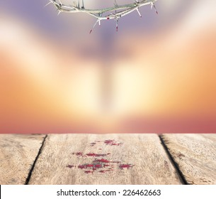 Forgive concept: Crown of thorns and drops of blood on wood table over blurred cross on a sunset background