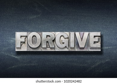 forgive word made from metallic letterpress on dark jeans background