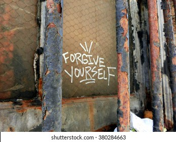 """Forgive yourself"" written behind rusty metal window bars - landscape color photo"