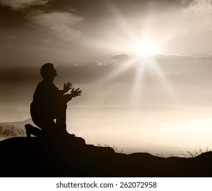 Forgiveness concept: Silhouette prayer kneeling and praying to God over supernatural light autumn background