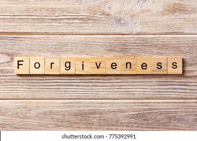 forgiveness word written on wood block. forgiveness text on table, concept.