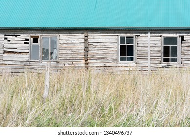 Forgotten abandoned wooden house exterior with broken smashed windows and a green metal roof