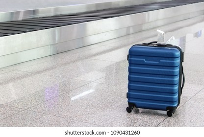 A forgotten lost suitcase in the airport hall. One case stands on wheels at the luggage transporter belt.