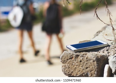 forgotten smart phone at summer holiday destination, lost smartphone, two girls leaving lost cell phone on a wall, selective focus