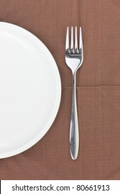 Fork and dish on a napkin as a dining room serving.