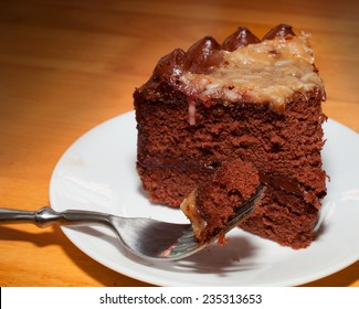 Fork full of chocolate cake that has coconut frosting