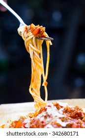 Fork full of twirled Italian spaghetti with a Bolognese meat sauce and basil suspended in the air above a full plate of food against a grey background