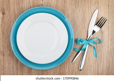 Fork with knife and blank plates. On wooden table background