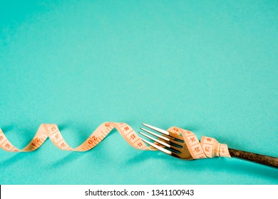 fork and knife with a centimeter on a blue background, diet, healthy lifestyle