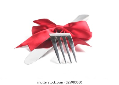Fork and knife with christmas ribbon, isolated on white, shallow focus
