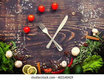 Fork with knife as the clock hands and tomatoes instead of figures at board. Concept time to eat