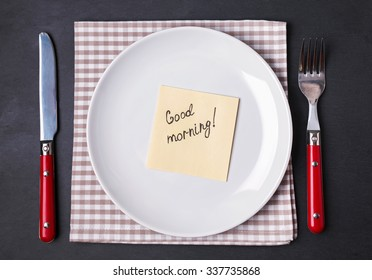Fork, knife and empty plate with paper note with text. Good morning concept.