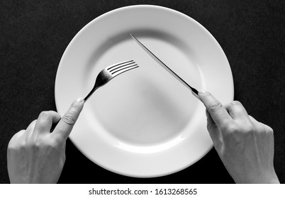 Fork and knife in hands black and white.