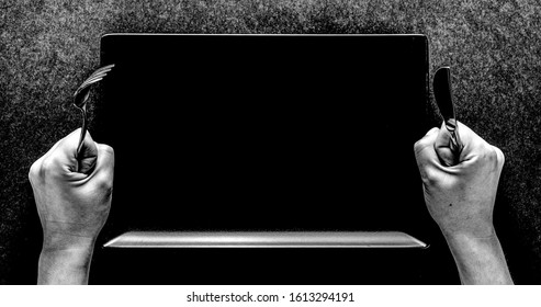 Fork and knife in hands on black background with black rectangular plate.