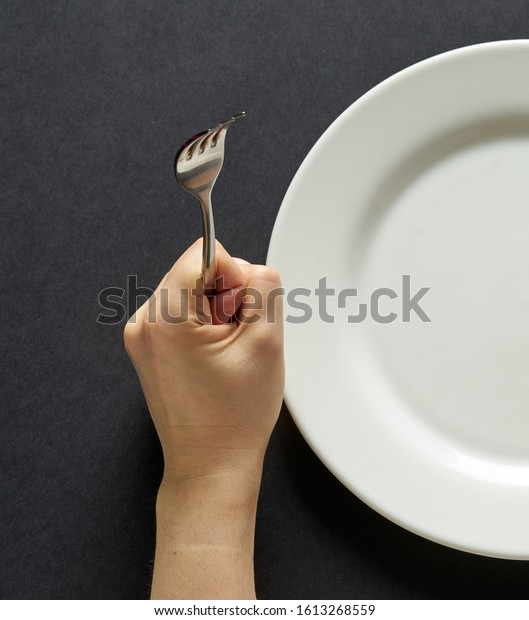 Fork and knife in hands on black background with white plate.