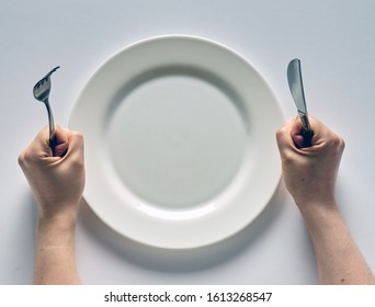 Fork and knife in hands on white background with white empty plate.