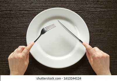 Fork and knife in hands on wooden background with white plate