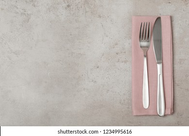 Fork, knife and linen napkin on grey background, top view. Space for text