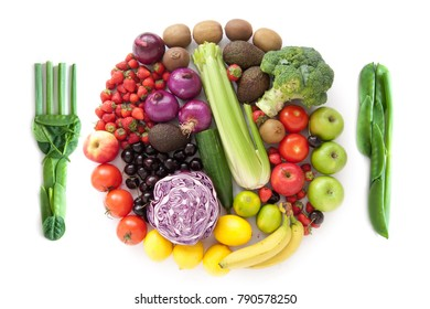 Fork and knife and miniature fruits and vegetables packed together in the shape of a plate