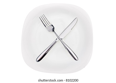 Fork and knife on a dish isolated on white background