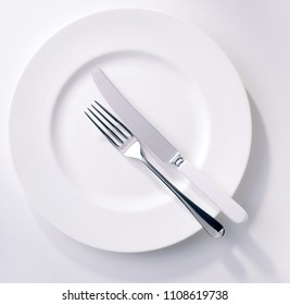 Fork and knife on a empty plate- top view