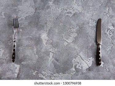 Fork and knife on grunge concrete background with copyspace