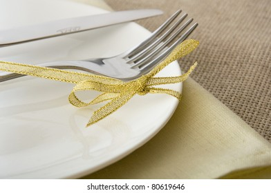 fork and knife on a white plate with a gold ribbon