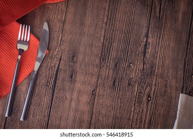Fork and knife on wooden table with kitchen towel.Top view