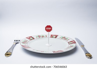 Fork, knife, plate on white background, and on the plate a stop sign.Copy space.
