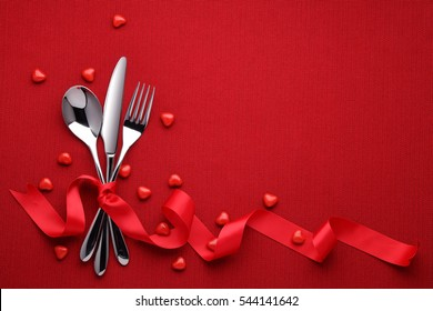 Fork knife spoon with ribbon on red