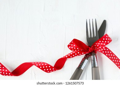 Fork and knife tied with a red ribbon on white background with copy space. Food, restaurant and table setting theme, copy space