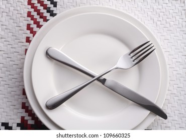 Fork and knife and white plate