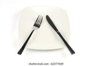 fork and knife in white plate isolated on background