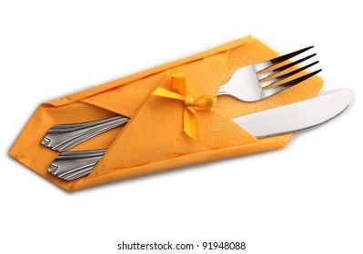 Fork and knife in a yellow cloth with a bow isolated on white