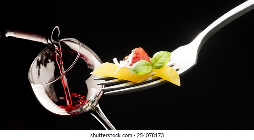 fork with macaroni glass of red wine on black background