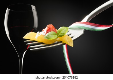 fork with macaroni tomato sauce and glass of red wine on dark background