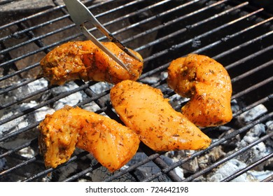 Fork and marinated chicken on the rack of a barbecue