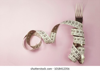 Fork and measuring tape isolated on pink