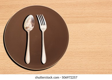 Fork on a dish Brown at wooden table.