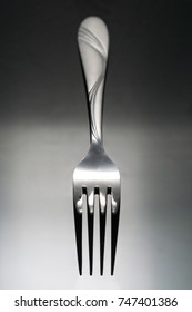 Fork on glossy black table surface background